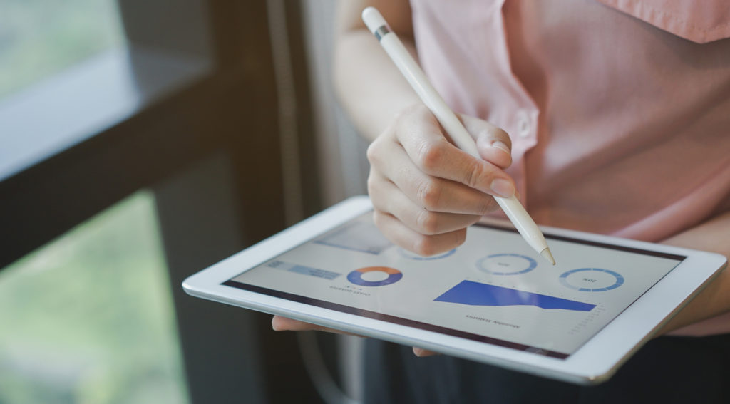 A woman using a tablet and stylus to review KPIs on a dashboard for her medical practice.